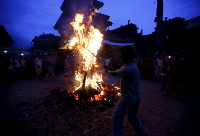People set fire to an effigy of the demon Ghantakarna, during the Ghantakarna festival at the ancient city of Bhaktapur, Nepal August 12, 2015. (Photo by Navesh Chitrakar/Reuters)