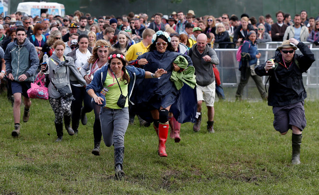 Revellers rush to the stage ahead of the performance of the Orchestra of Syrian Musicians with Damon Albarn and guests on the Pyramid stage at Worthy Farm in Somerset during the Glastonbury Festival, Britain, June 24, 2016. (Photo by Stoyan Nenov/Reuters)