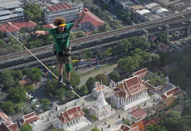 Slackliner, Andy Lewis of the US balances as he walks on a highline from the rooftop of a building in Bangkok on July 23, 2014. Lewis set a world record after walking on a highline from the rooftop of a building to another covering a distance of 169 metres in one hour and five minutes. (Photo by Pornchai Kittiwongsakul/AFP Photo)
