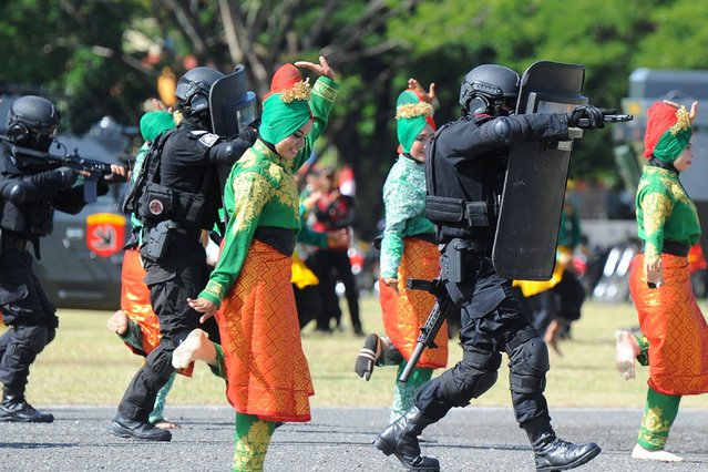 Police from the anti- terror squad participate in an anti- terror performance among Acehnese dancers during a ceremony to commemorate the 71 st anniversary of the Indonesian police corps in Banda Aceh on July 10, 2017. (Photo by Chaideer Mahyuddin/AFP Photo)
