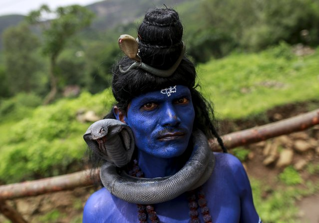 """A devotee dressed as Hindu Lord Shiva waits to participate in a parade during """"Kumbh Mela"""" or the Pitcher Festival in Trimbakeshwar, India, August 18, 2015. The Kumbh Mela takes place four times every 12 years at four different river bank locations in India. (Photo by Danish Siddiqui/Reuters)"""