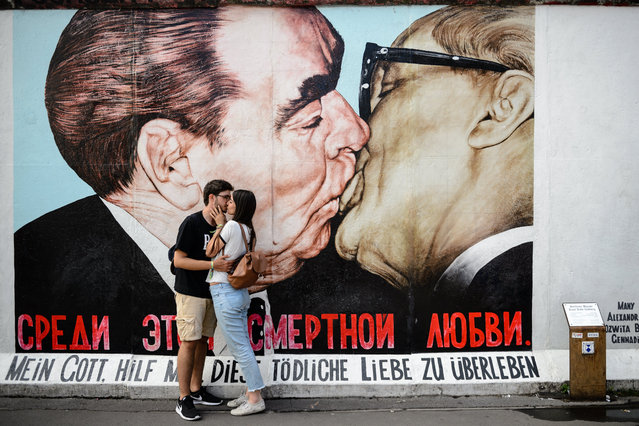 "Tourists kiss in front of the graffiti painting ""My God, Help Me to Survive This Deadly Love"" by Russian Dmitri Vrubel at a section of the former Berlin Wall called the East Side Gallery in Berlin, Germany, 10 August 2017. The artwork also known as the ""Fraternal Kiss"" (""Bruderkuss"" in German) depicts the kissing communist leaders Leonid Brezhnev of the Soviet Union and Erich Honecker of the GDR. The former East German communist regime started the construction of the Berlin Wall on 13 August 1961, 56 years ago. The Wall came down on 09 November 1989. (Photo by  Jens Schlueter/EPA)"