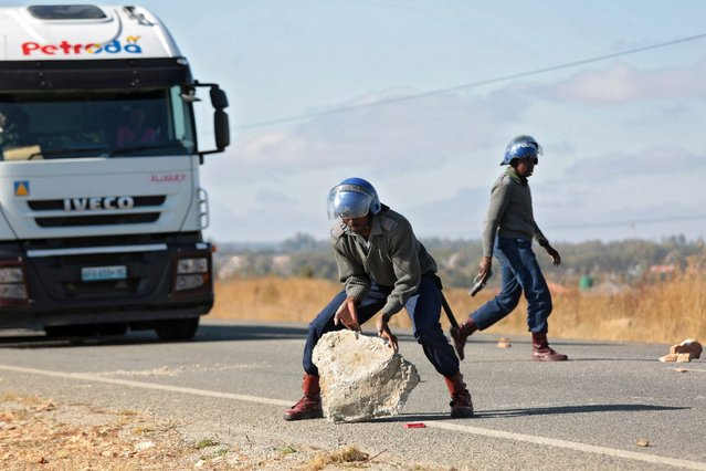 A police officer removes a stone from Mutare road outside Harare, Zimbabwe, 04 July 2016. In a protest over frequently blocked street, operators of commuter buses themselves blocked roads with stones, burning tyres and other objects. (Photo by Aaron Ufumeli/EPA)