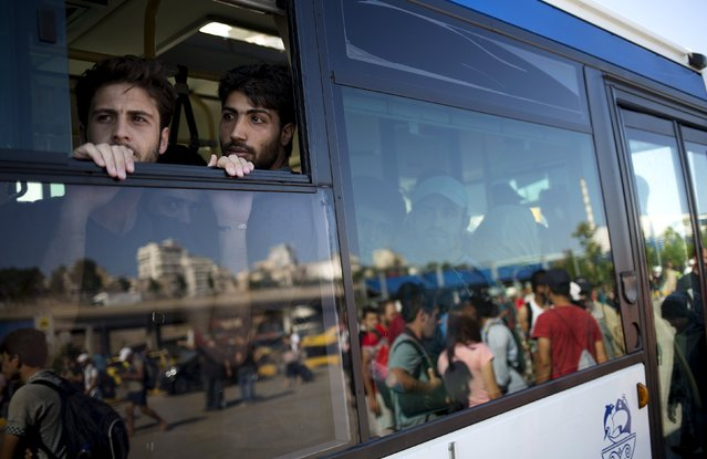 """Syrian refugees look out from a bus window following their arrival onboard """"Eleftherios Venizelos"""" passenger ship at the port of Piraeus near Athens, Greece, August 20, 2015. (Photo by Stoyan Nenov/Reuters)"""