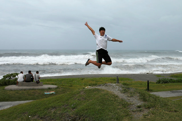 A man jumps as his father takes a photo in front of the coast as Typhoon Nepartak approaches in Yilan, Taiwan July 7, 2016. (Photo by Tyrone Siu/Reuters)