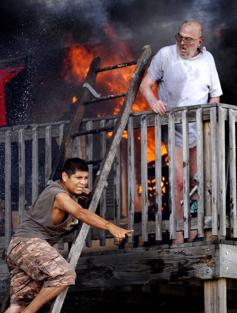 Edwardo Martinez yells for help as he tries to rescue Pete Lui off the balcony of Lui's home in Racine, Wisconsin, as flames spread through the second floor apartment on July 24, 2012. (Photo by Gregory Shaver/Journal Times)