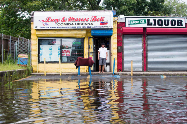 A person surveys flood water outside Lucy & Marcos Deli following heavy rains and flash flooding on August 13, 2014 in Bayshore, New York. The south shore of Long Island along with the tri-state region saw record setting rain that caused roads to flood entrapping some motorists. (Photo by Andrew Theodorakis/Getty Images)