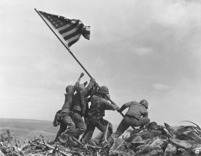 U.S. Marines of the 28th Regiment, 5th Division, raise the American flag atop Mt. Suribachi, Iwo Jima, on February 23, 1945. Strategically located only 660 miles from Tokyo, the Pacific island became the site of one of the bloodiest, most famous battles of World War II against Japan. This iconic photo won Joe Rosenthal the Prize in 1945. (Photo by Joe Rosenthal/AP Photo)