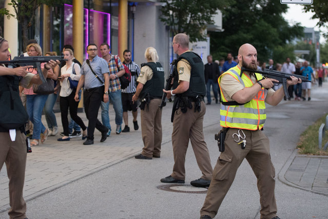 Police escort people who leave the Olympia mall in Munich, southern Germany, Friday, July 22, 2016 after shots were fired. Police said that at least six people have been killed. (Photo by Sebastian Widmann/AP Photo)