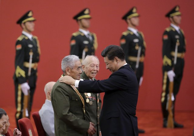 China's President Xi Jinping presents a commemorative medal to a veteran Shi Baodong at a medal ceremony marking the 70th anniversary of the Victory of Chinese People's War of Resistance Against Japanese Aggression, for World War Two veterans, at the Great Hall of the People in Beijing, China, September 2, 2015. (Photo by Jason Lee/Reuters)