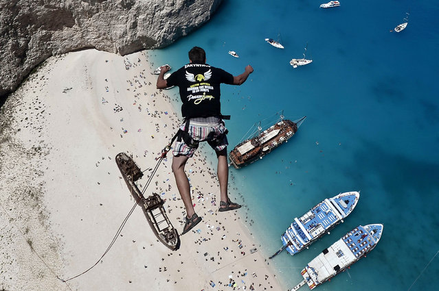 "Lukas Michul, a member of the ""dream walker"" group jumps from atop the rugged rocks overlooking the azure waters of Navagio beach, one of the Greece's most renowned leisure spots on the popular tourist island of Zakynthos on June 23, 2014. (Photo by Louisa Gouliamaki/AFP Photo)"
