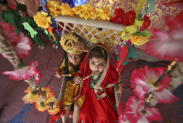 Schoolchildren dressed as Lord Krishna (L) and his consort Radha take part in celebrations to mark the Janmashtami festival in Jammu August 27, 2013. (Photo by Mukesh Gupta/Reuters)