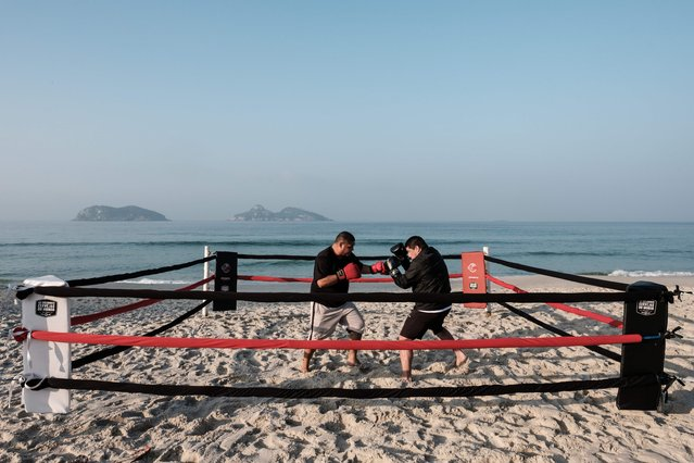 Boxing trainer Moacyr Lima (L) trains Leandro Guignoni in beach boxing at Pepe beach in Rio de Janeiro, Brazil, on July 26, 2016. Since Lima first installed a ring on a beach at the end of last year, beach boxing has attracted fitness enthusiasts from amature to professional fighters. Lima created the Rio de Janeiro State Beach Boxing Federation (FEBOP) and signed a contract with a cable channel for broadcasting the tournaments. (Photo by Yasuyoshi Chiba/AFP Photo)