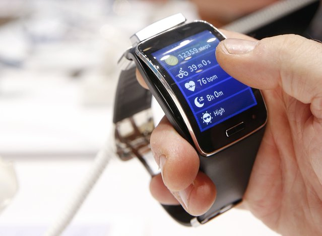A visitor holds a Samsung Gear S smartwatch at the IFA consumer technology fair in Berlin, September 5, 2014. (Photo by Fabrizio Bensch/Reuters)