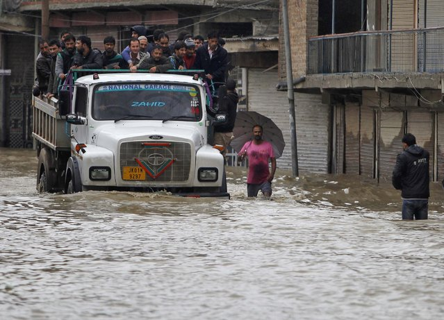Kashmiri people use a truck to move to safer places through a flooded street after heavy rain in Srinagar September 6, 2014. Authorities declared a disaster alert in the northern region after heavy rain hit villages across the Kashmir valley, causing the worst flooding in two decades. (Photo by Danish Ismail/Reuters)