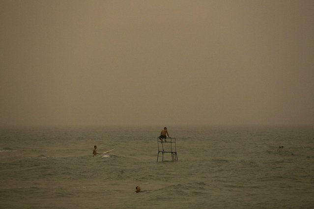 Beachgoers bathe in the Mediterranean Sea during a sandstorm in Ashkelon, Israel September 8, 2015. (Photo by Amir Cohen/Reuters)