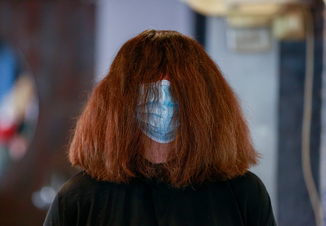A costumer in a protective mask at the hair saloon 'Le Studio', in Brussels, Belgium, 18 Mai 2020. Belgium eased lockdown measures in place to curb the spread of the COVID-19. (Photo by Stéphanie Lecocq/EPA/EFE)