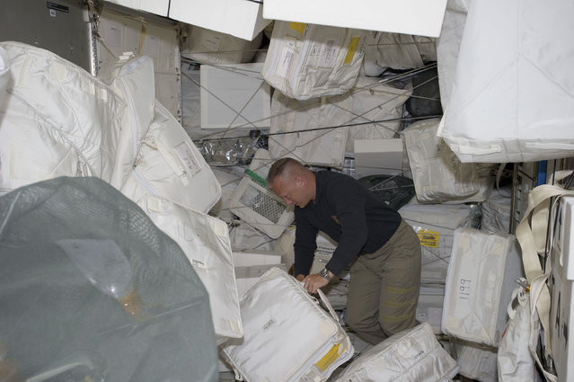 Space shuttle Atlantis Pilot Doug Hurley moves around supplies and equipment in the Leonardo Permanent Multipurpose Module of the International Space Station on July 11, 2011. (Photo by Reuters/NASA)
