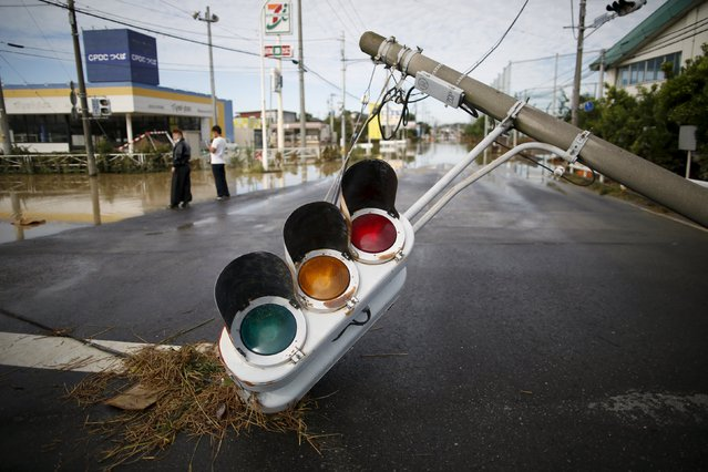 A damaged traffic signal is pictured along a street at a residential area flooded by the Kinugawa river, caused by typhoon Etau in Joso, Ibaraki prefecture, Japan, September 11, 2015. Unprecedented rain in Japan unleashed heavy floods on Friday that tore houses from their foundations, uprooted trees and forced more than 100,000 people from their homes. (Photo by Issei Kato/Reuters)