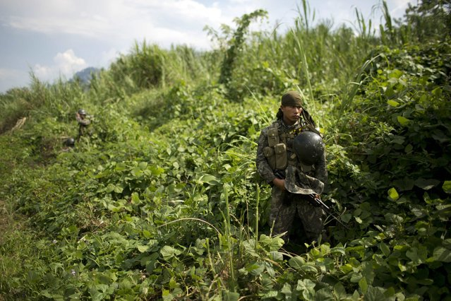 In this September 19, 2014 photo, a soldier stands guard during the destruction of a clandestine airstrip in the Valley of the Apurimac, Ene and Mantaro River Valleys, or VRAEM, the world's No. 1 coca-growing region in Ayacucho, Peru. Peruvian and Bolivian officials have agreed during a meeting in La Paz to share information in real time on cross-border drug flights. They did not, however, divulge details. (Photo by Rodrigo Abd/AP Photo)