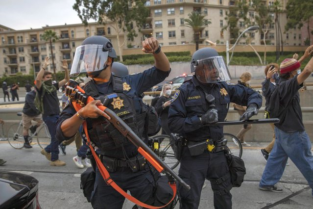 Police officers hold their position as protesters march by in Los Angeles, Friday, May 29, 2020, in protest over the death of George Floyd, who died in police custody on Memorial Day in Minneapolis. (Photo by Christian Monterrosa/AP Photo)