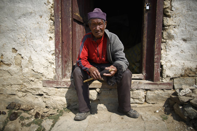 Khunjung Sherpa, 90, who earned 0.09 USD a day when he worked as a porter, sits outside his house in Namche, Solukhumbu District April 27, 2014. (Photo by Navesh Chitrakar/Reuters)