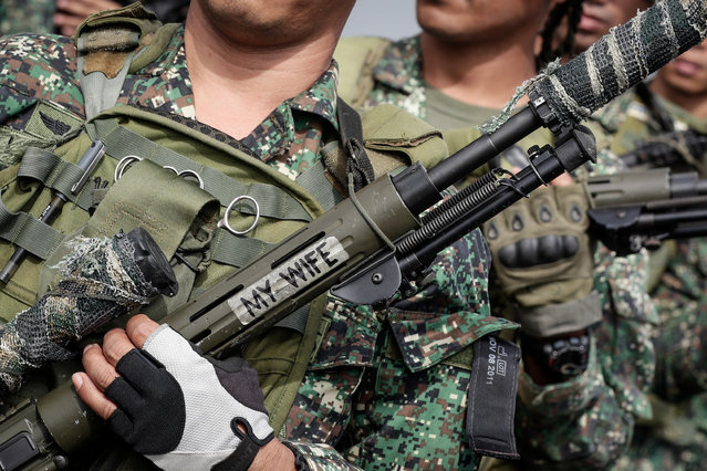 """A close-up picture shows a gun of a soldier with a sticker from the Fleet-Marine contingent who were deployed in Marawi during their arrival at a port in Manila, Philippines, 30 October 2017. The Fleet-Marine, composed of more than 500 sailors, marines, seals, aviators, intelligence and civil military operations were given a heroes welcome by the Philippine Navy upon their arrival after a five month deployment in Marawi. Philippine President Rodrigo Duterte on 17 October declared the city of Marawi liberated after five months of fighting between the Philippine armed forces and rebels allied with the so-called """"Islamic State"""", or IS. (Photo by Mark R. Cristino/EPA/EFE)"""
