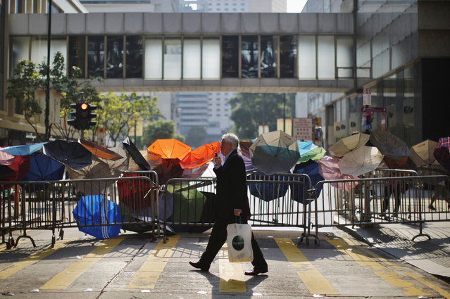 A man walks by a barricade of metal fence and umbrellas on a street at the central financial district, near the government headquarters in Hong Kong September 30, 2014. (Photo by Carlos Barria/Reuters)