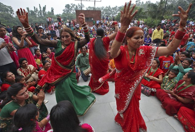 Nepalese Hindu women dance during celebrations for the Teej festival in Chandigarh, India, September 16, 2015. Nepalese Hindu women all over the world fast and pray for the good health and longevity for their husbands during the festival. (Photo by Ajay Verma/Reuters)