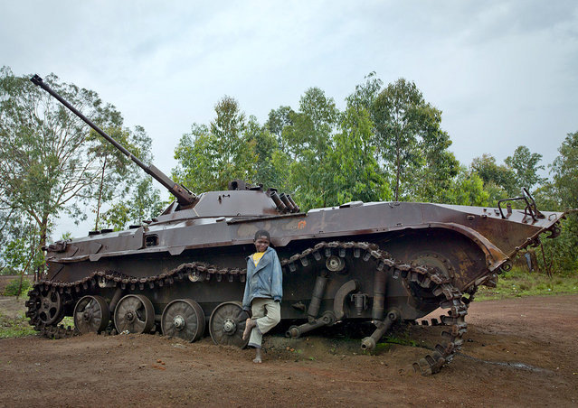 """Souvenir from the civil war – Angola. Hundreds of tanks can still be seen all around Angola, even in town, like in Huambo. And of course, the kids use them as giant toys! Adults use it as a giant bin""... (Eric Lafforgue)"