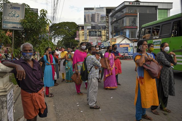 People wearing masks as a precaution against the coronavirus wait for transportation in Kochi, Kerala state, India, Thursday, June 25, 2020. India is the fourth hardest-hit country by the COVID-19 pandemic in the world after the U.S., Russia and Brazil. (Photo by R.S. Iyer/AP Photo)
