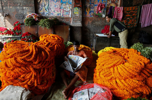 A man reads a newspaper next to marigold garlands, which are used to decorate temples and homes, at a wholesale flower market in Kolkata, India, November 21, 2017. (Photo by Rupak De Chowdhuri/Reuters)