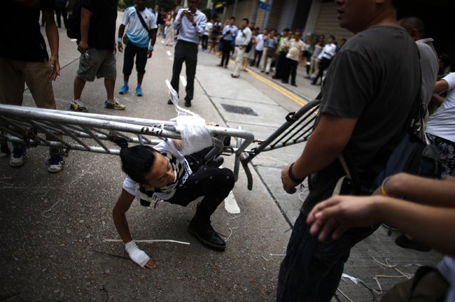 Anti-Occupy Central protesters drag a metal fence over a pro-democracy protester (C) at the main protest site in Admiralty in Hong Kong October 13, 2014. (Photo by Carlos Barria/Reuters)