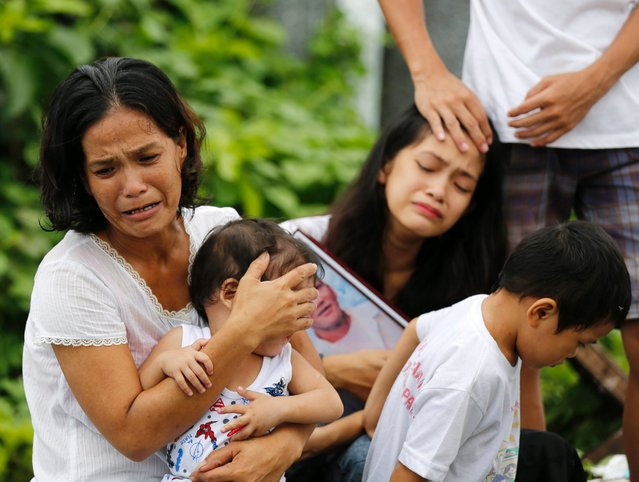 Filipino relatives of a slain alleged drug dealer, who was killed during a police operation against illegal drugs, mourn during burial rites at Manila North Cemetery, Manila, Philippines, August 28, 2016. (Photo by Francis R. Malasig/EPA)