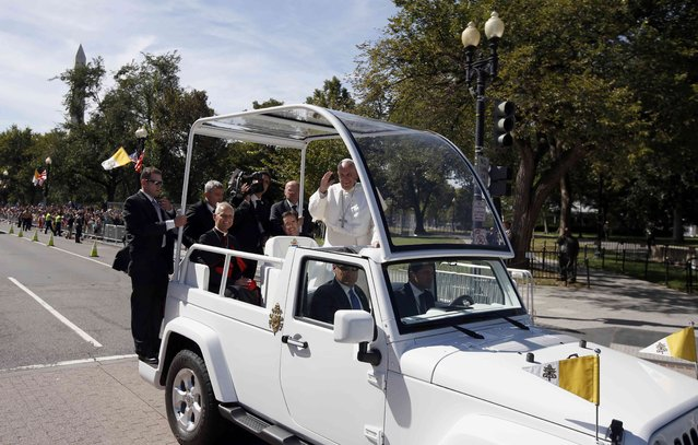 Pope Francis waves from the popemobile during a papal parade in Washington September 23, 2015. (Photo by Alex Brandon/Reuters)
