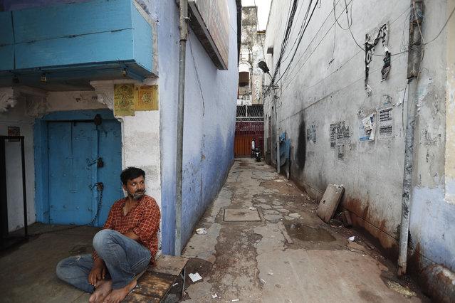 A man sits on a deserted street during fresh lockdown in Prayagraj, India, Saturday, July 11, 2020. (Photo by Rajesh Kumar Singh/AP Photo)