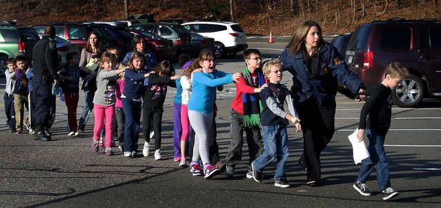 Connecticut State Police lead a line of children from the Sandy Hook Elementary School after the shooting at the school. (Photo by Shannon Hicks/Newtown Bee)