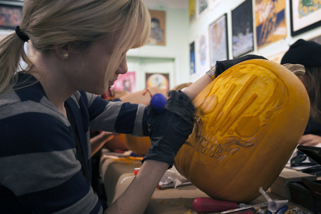 A workshop attendee is carving a ZeroFriend design on her pumpkin at Cotton Candy Machine in Brooklyn, N.Y. on October 18, 2014. (Photo by Siemond Chan/Yahoo Finance)