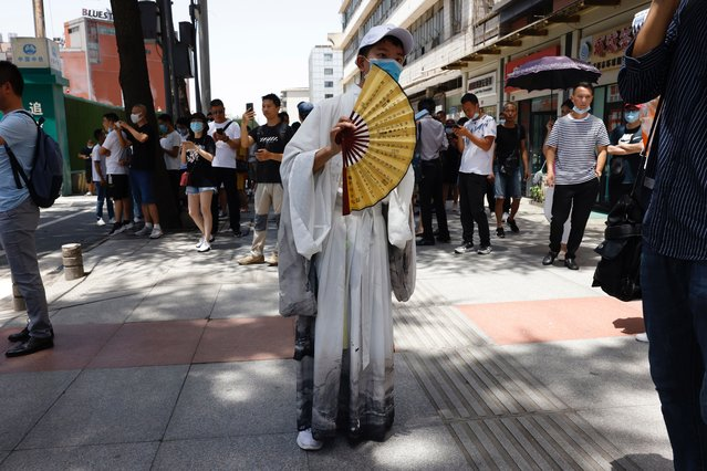A resident peers from behind a fan as he joins a crowd gathered outside the United States Consulate in Chengdu in southwest China's Sichuan province on Sunday, July 26, 2020. (Photo by Ng Han Guan/AP Photo)
