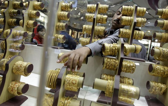 An Indian salesman collects a bangle to present to a customer at a jewelry shop in the gold suq in Dubai, United Arab Emirates. Dubai's tax-free status has made it one of the cheapest places in the world to buy gold and  has also become a retail center with 600 shops selling gold – half of them crammed into the gold souq – drawing tourists, traders and local residents. (Photo by Kamran Jebreili/AP Photo)