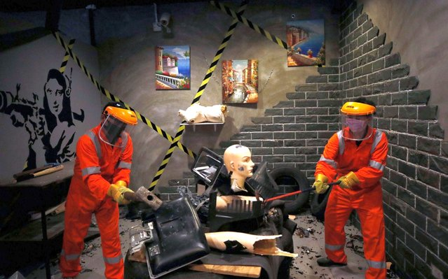 Thai customers destroy items to vent anger and release stress at the Rage Room in Bangkok, Thailand, 25 July 2020. The new opening Rage Room offers the chance for angry people to vent their anger, frustration and relieve stress by ruining everything and destroying various objects including television, radio, mannequin, office supplies and old appliances with selection tools as baseball bat, golf club, iron bar, hammer and more. (Photo by Rungroj Yongrit/EPA/EFE)