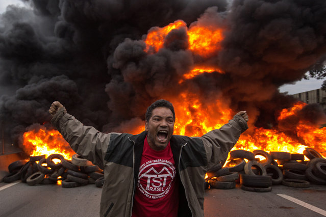 Members of the Workers Without a Roof Movement (MTST) burn tyres to block the Presidente Dutra road during a protest in Guarulhos, Brazil, 02 August 2017. Reports state that demonstrators aimed to press the Chamber of Deputies the day they decide whether Brazilian President Michel Temer will be prosecuted for corruption. (Photo by Sebastiao Moreira/EPA/EFE)