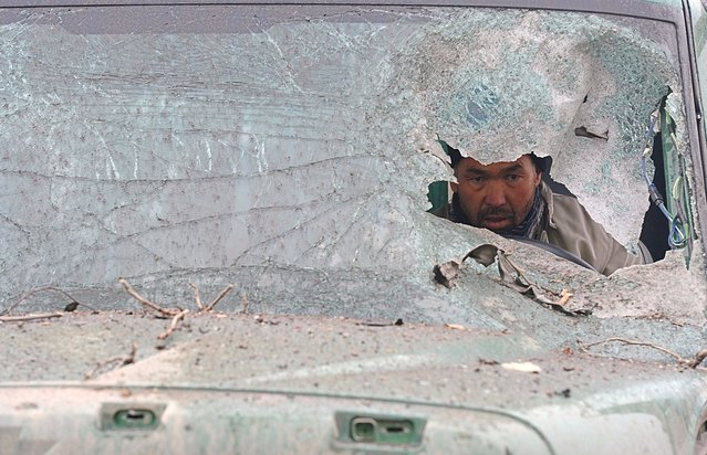 An Afghan truck driver is seen through the broken windshield of his vehicle at the site of a suicide attack near the Afghan intelligence agency headquarters in Kabul. A squad of suicide bombers attacked the national intelligence agency headquarters in heavily-fortified central Kabul on January 16, killing at least two guards and wounding dozens of civilians, officials said. (Photo by Shah Marai)
