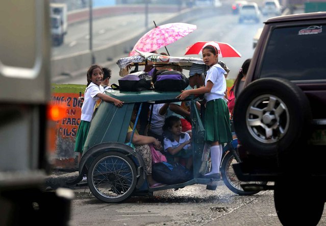 Filipino schoolchildren hang on to an overloaded tricycle on a busy road on their way to school in Manila, Philippines, Monday, October 5, 2015. Inadequate public transportation in the Philippines sometimes force commuters to risk traveling by hanging on the side and even sitting atop passenger buses, jeeps and smaller vehicles to get to their destination. (Photo by Aaron Favila/AP Photo)