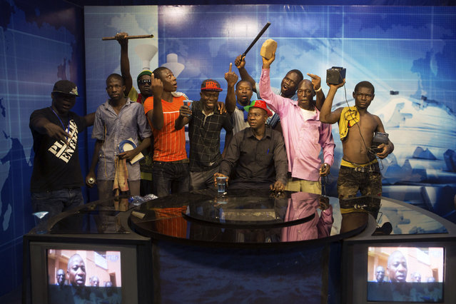 Anti-government protesters take over the state TV podium in Ouagadougou, capital of Burkina Faso, October 30, 2014. (Photo by Joe Penney/Reuters)