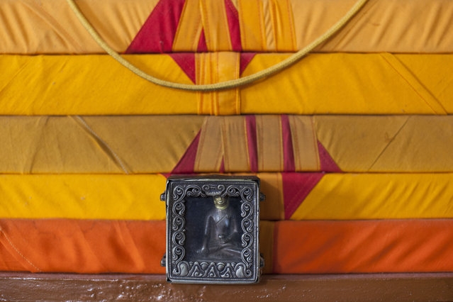 "In this Tuesday, September 30, 2014 photo, an amulet containing a Buddha statue stands near scriptures in the home of Tibetan exile Sonam Gyaltsen, 44, near Dharamsala, India. Gyaltsen, who is now a member of the Tibetan parliament-in-exile, carried the amulet with him as a family keepsake when he escaped into India in 1993. ""There is technology that connects me to my family back home in Tibet now but I worry about their health"", he said. (Photo by Tsering Topgyal/AP Photo)"