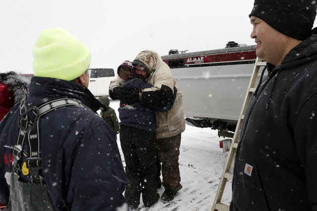 In this October 7, 2014, photo, Qaiyaan Aiken, center, gets a hug from his wife as he is congratulated for harpooning a bowhead whale after making his way back to shore near Barrow, Alaska. The crews that bring in a whale are celebrated in town, and their stories of exactly how the whale was harpooned are heard throughout town. (Photo by Gregory Bull/AP Photo)