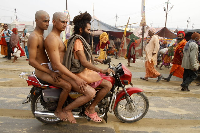 "Two Hindu holy men of the Juna Akhara sect  are being take on a motorcycle by their teacher as they got delayed for a rituals that are believed to rid them of all ties in this life and dedicate themselves to serving God as a ""Naga"" or naked holy men, at Sangam, the confluence of the Ganges and Yamuna River during the Maha Kumbh festival in Allahabad, India, Wednesday, February 6, 2013. (Photo by Rajesh Kumar Singh/AP Photo)"