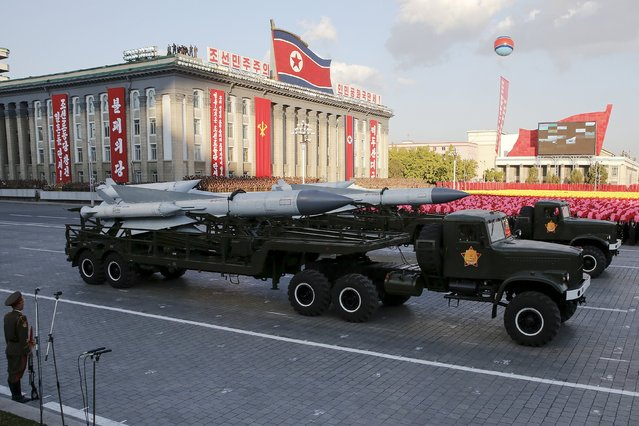 Missiles are taken on trucks past a stand with North Korean leader Kim Jong Un during the parade celebrating the 70th anniversary of the founding of the ruling Workers' Party of Korea, in Pyongyang October 10, 2015. (Photo by James Pearson/Reuters)