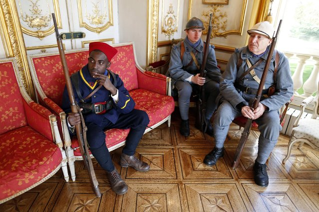 """World War One historical enthusiasts dressed in vintage army uniforms as """"Poilu"""" (French soldier during World War I) sit inside the town hall during an Armistice Day ceremony to commemorate the end of World War One at Epernay, eastern France, November 11, 2014. (Photo by Charles Platiau/Reuters)"""
